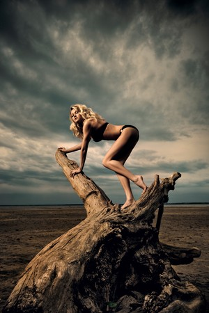 Afternoon woodclimbing. A woman climbing on driftwood on the beach. photo