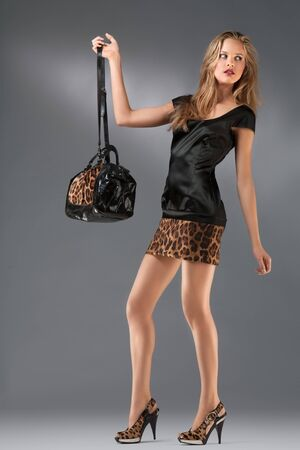 szoknya: Leopard revolution. A studio portrait of a sexy hot lady in leopard clothes holding a bag.