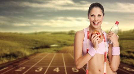 ropa deportiva: Corredor sexy. Una joven atl�tica celebraci�n de agua y manzana contra la pista de atletismo.  Foto de archivo