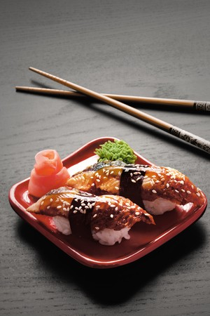 eel: Tempting nigiri. A close-up of chopsticks and a square plate with two pieces of eel nigiri, wasabi and ginger. Stock Photo
