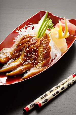 Sashimi boat. A close-up of chopsticks and a sashimi boat with eel sashimi, daikon, lemon, wasabi and ginger. photo