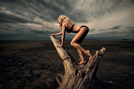driftwood: Afternoon woodclimbing. A woman climbing on driftwood on the beach.