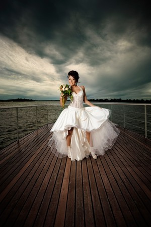e pretty: Nubile fiancée! A pretty young lady on deck in a white wedding dress holding a wedding bouquet. Stock Photo