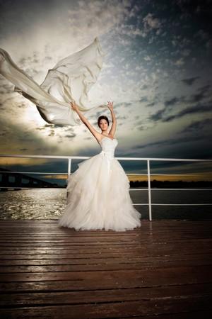 Fiancé in the wind. Pretty lady in a wedding dress on deck. photo