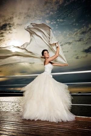 Fiancé in the wind. Pretty lady in a wedding dress on deck. Banco de Imagens