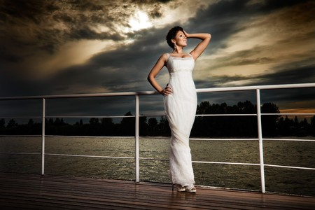 luxury yacht: Glamorous bride. Pretty lady in a white evening dress on deck. Stock Photo