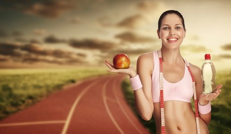 healthy life: A young athletic woman holding water and apple against running track. Stock Photo