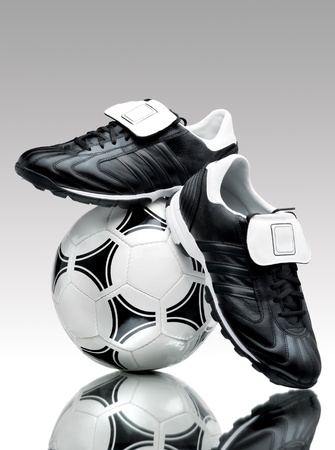 a pair of: A pair of cool football boots standing on a ball on a reflective surface.