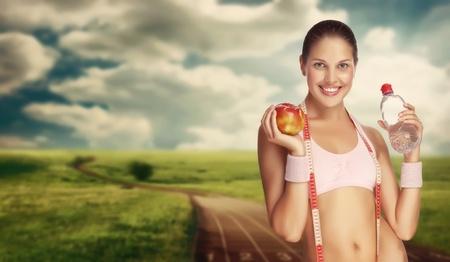 Una joven atlética con agua y apple contra la pista de atletismo.