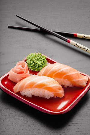 wasabi: A close-up of chopsticks and a square plate with two pieces of salmon nigiri, wasabi and ginger. Stock Photo