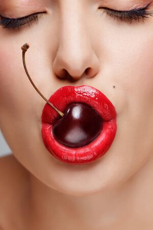 A closeup of a young pretty women face holding a yummy cherry in her mouth. Stock Photo - 9239661