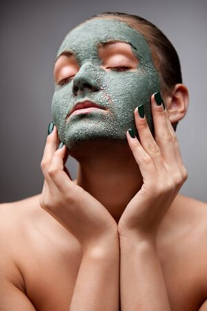 A portrait of a beautiful relaxing lady  with a clay mask on her face. photo