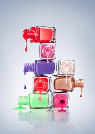 cosmetic lacquer: Nail polish dripping from stacked bottles.