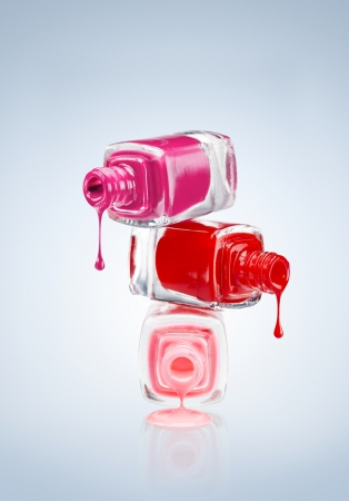 Colour splash! A colorful pyramid of three open nail polish bottles of different colors with flowing drops. photo