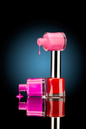 Juicy drops! Three nail polish bottles of bright colors with juicy falling drops against black background. photo
