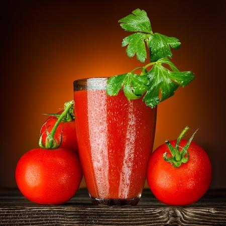 Rot und nass! Ein nasses Glas Tomatensaft dekoriert mit Petersilie und reife Tomaten Bündel auf einem Holztisch.