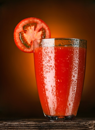 Bloody shake! A wet glass full of tomato juice decorated with a slice of tomato standing on a wooden table.