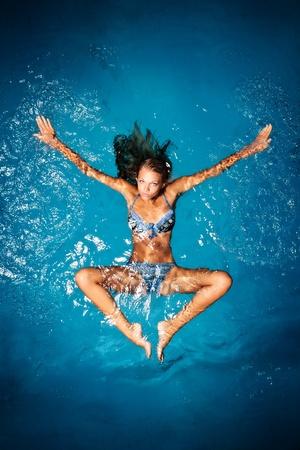teknik: En sexig solbränd kvinna i en färgglad bikini poserar i en simbassäng.