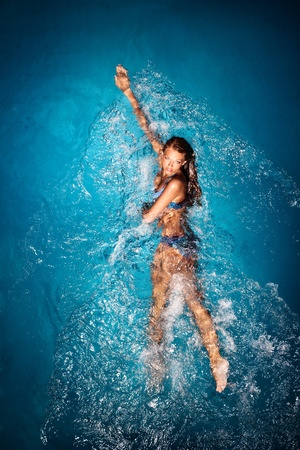 A sexy tanned lady in a colorful bikini posing in a swimming pool. Stock Photo