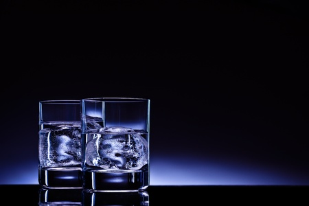 Two glasses of vodka with ice cubes against the background of deep blue glow. Stock Photo - 10689861