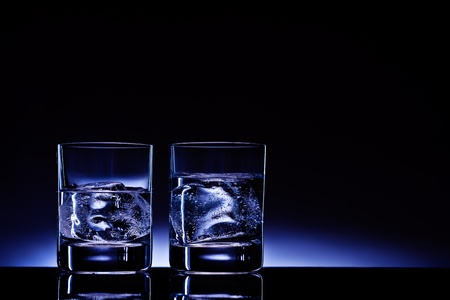 alcoholic beverage: Two glasses of vodka with ice cubes against the background of deep blue glow.