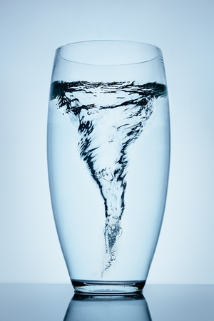 whirlpools: Magnificent tornado made of water in a transparent glass standing on the reflective surface. Stock Photo