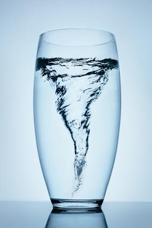 Prachtige tornado gemaakt van water in een transparant glas staan op het reflecterende oppervlak.