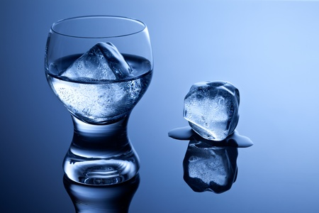 An elegant shot glass with vodka and ice along with a melting ice cube on reflective surface.