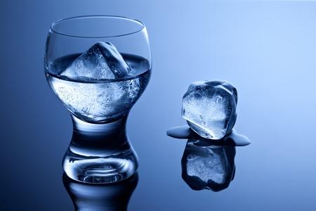 melting ice: Un elegante vaso con vodka y el hielo junto con un cubo de hielo que se derrite en la superficie reflectante. Foto de archivo