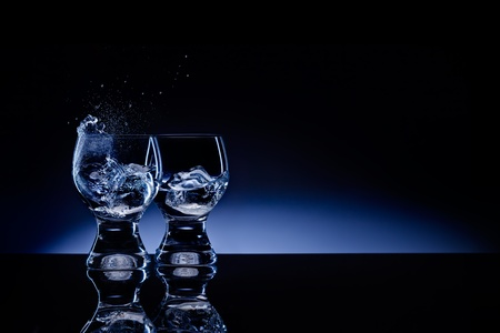 A picture of two shaped transparent shot glass with choppy liquid and ice. photo