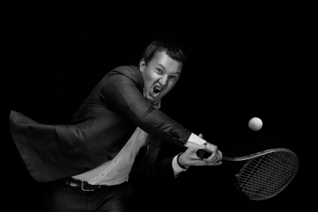 A portrait of a tanned businessman tennis player with a racket against black background. photo
