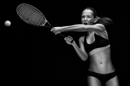 Female tennis player with racket ready to hit a tennis ball. photo