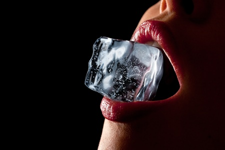 Ice cube in a womans mouth against black background.
