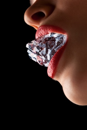 Ice cube in a woman's mouth against black background. Stock Photo - 13406707