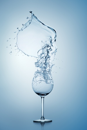 Water splashing into or out of a stemmed wine glass