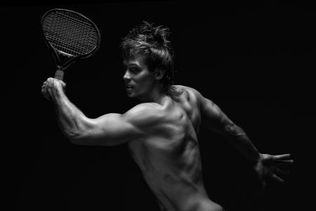 tenis: Un retrato de un jugador de tenis curtidos deportivo con una raqueta contra el fondo negro. Foto de archivo