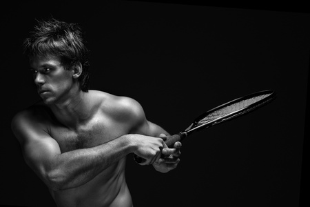 A portrait of a tanned sportive tennis player with a racket against black background. photo