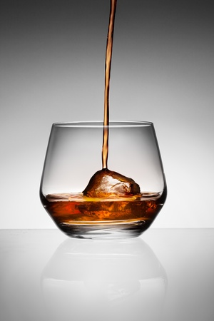 Side view of whisky pouring on ice in glass, studio background  photo