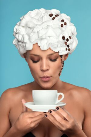 A young lady in a whipped cream on her head with a coffee cup  Stock Photo - 15140394