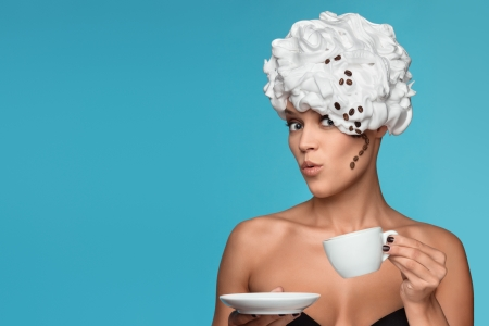 A young lady in a whipped cream on her head with a coffee cup  photo