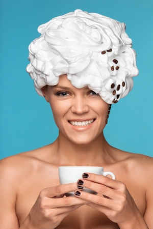 A young lady in a whipped cream on her head with a coffee cup