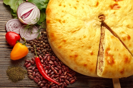 Ossetian cuisine. Kadurdjin meat pie and vegetables on wood. photo