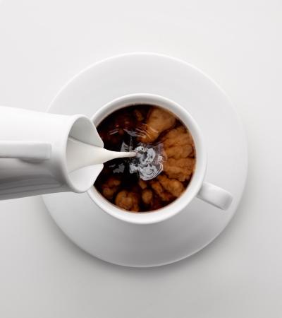 Gesünder mit Milch Hinzufügen Milch zu einer Tasse Kaffee