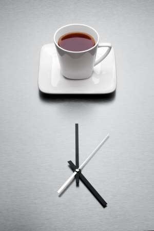 When the day is done the very teatime come - A white mug filled with tea over minimalistic clock  photo