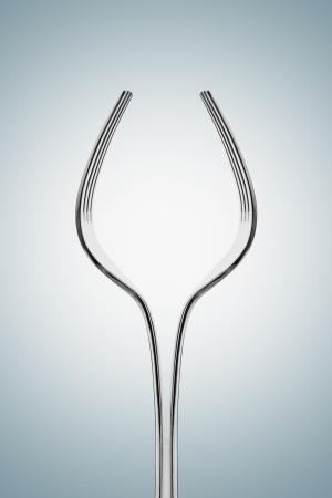 metaal: Twee zilveren vorken vormen groot glas wijn.
