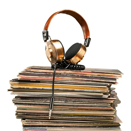 The symphony of soul - Golden headphones lying on the stack of vinyle records