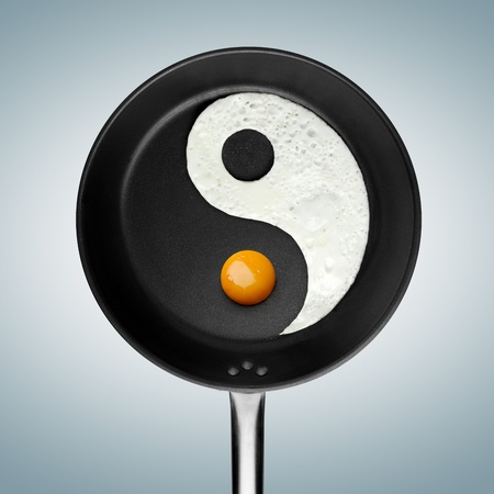 A fried egg philosophy - An yin-yan symbol made of fried egg in a pan  photo