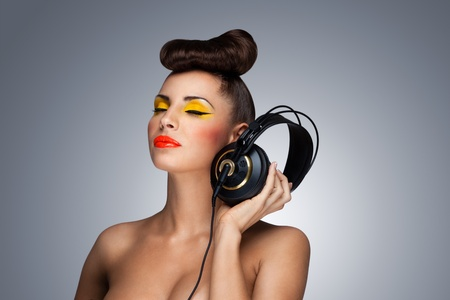 A lovely photo of beautiful girl holding headphones in her hand. photo