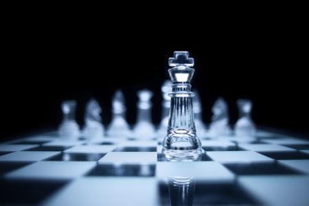 liderazgo empresarial: Foto del rey de ajedrez de pie delante del mismo color situado en el fondo negro