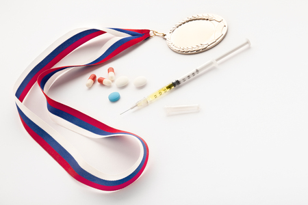A set of a winner with a syringe, doping pills and a gold prize medal. Stock Photo